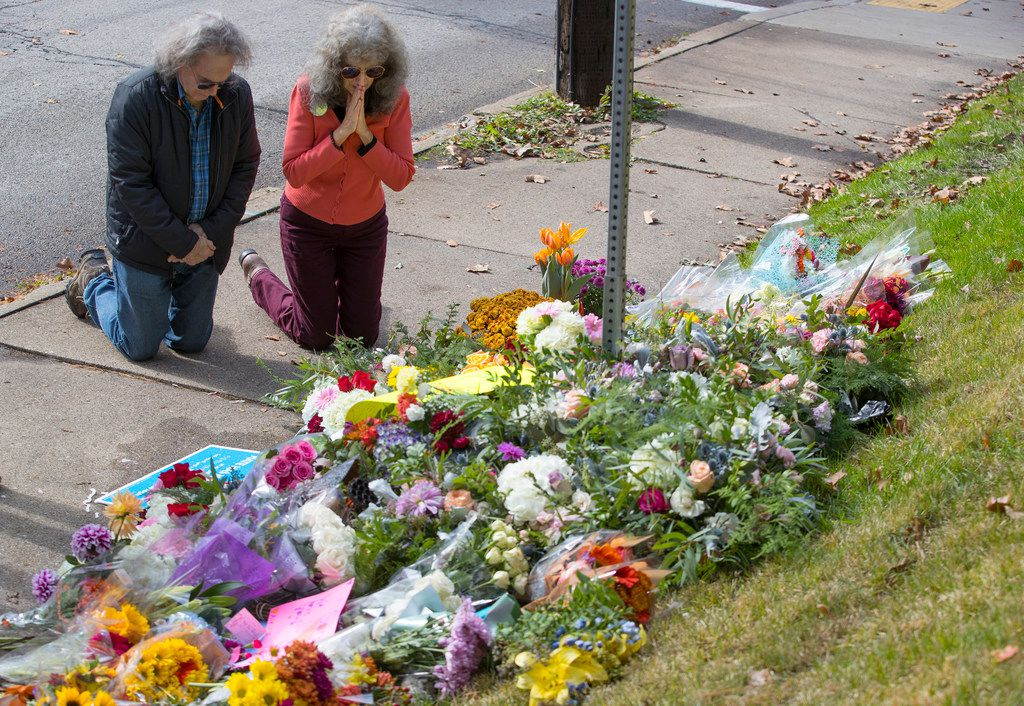 A couple kneels before a memorial at Murray and Wilkins avenues on Sunday, Oct. 28, 2018 in Pittsburgh. The memorial was for the 11 people that were killed at the shooting at the Tree of Life Synagogue.