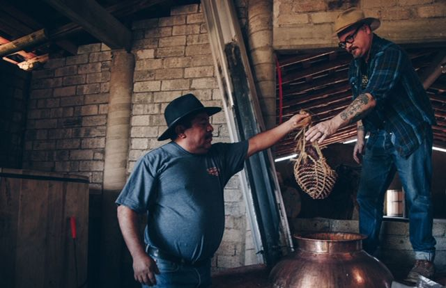 Gracias a Dios mezcalero Oscar Hernandez hands the basket containing the brisket and other ingredients to Las Almas Rotas' Kvetko to place into the still for the mezcal's final distillation.