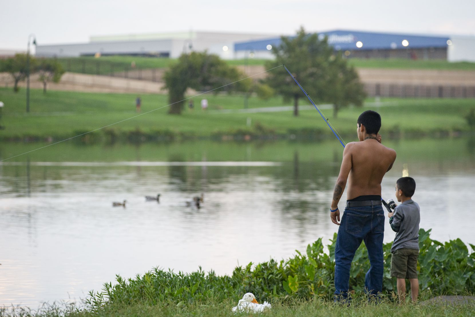Terrance Hunt gave son Milton Smith Ceren Mejía a fishing lesson at Bachman Lake last September. While some recreational activities are allowed at Bachman and White Rock Lake, swimming isn't among them.