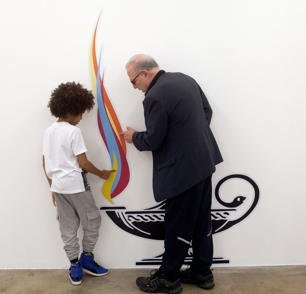 Benjamin Woods, 8, and Michael Corris examine Lit (2017), an inkjet-on-vinyl work, at Liliana Bloch Gallery in Dallas.