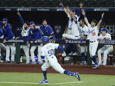 The Los Angeles Dodgers dugout erupts after right fielder Mookie Betts (50) hit a solo home run during the eighth inning against the Tampa Bay Rays in Game 6 of the World Series at Globe Life Field on Tuesday, Oct. 27, 2020.
