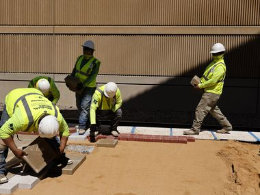 Construction workers remake the platform at DART's Mockingbird Station during U.S. Transportation Secretary Pete Buttigieg's visit to Dallas earlier this month. Scott Burns says a majority of all Americans would benefit from higher wages, even if it brings some inflation with it.