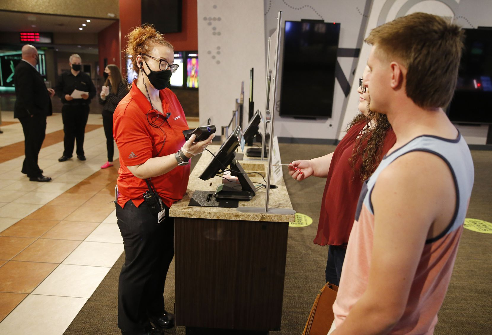 Cinemark's Jennifer Bell (left) scans the tickets of Hannah Potter (center) and Tony Johnson (right), the first customers in the building since the movie theater closed due to the coronavirus pandemic at Cinemark West in Plano, on Friday, June 19, 2020. After being closed for months due to the coronavirus pandemic, the theater reopened Friday. (Vernon Bryant/The Dallas Morning News)