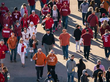 Fans walk through the fair grounds on their way to the stadium before an NCAA football game between Texas and Oklahoma at the Cotton Bowl on Saturday, Oct. 12, 2019, in Dallas. (Smiley N. Pool/The Dallas Morning News)