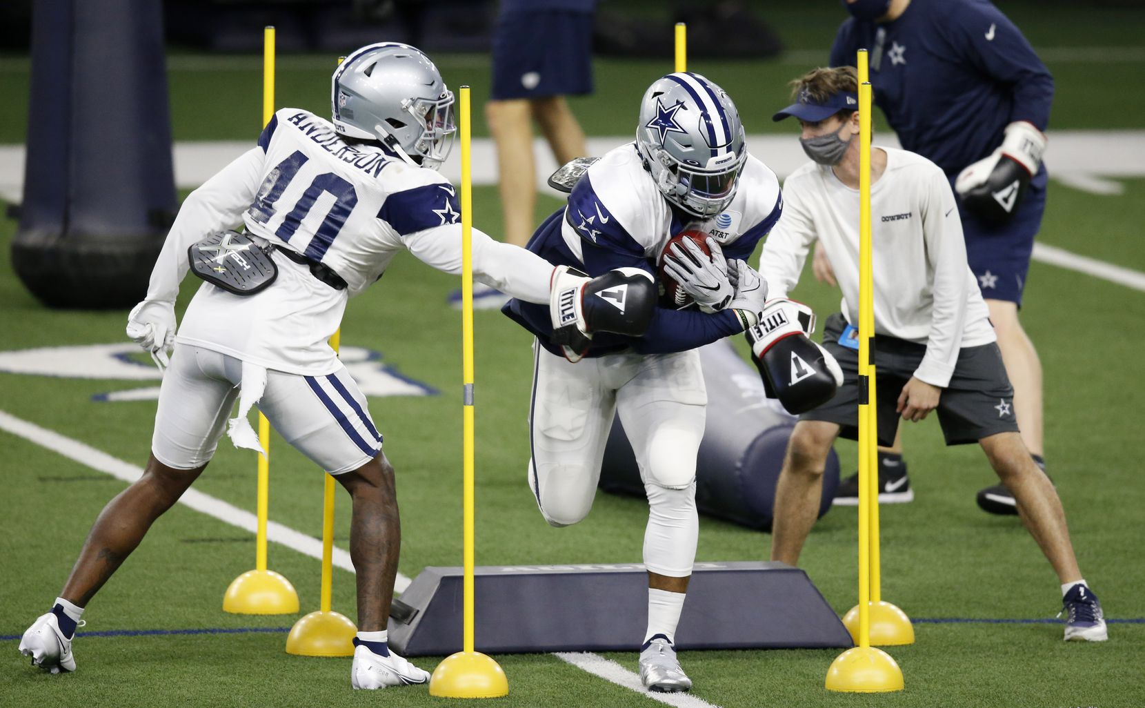 Dallas Cowboys running back Ezekiel Elliott (21) runs through a drill as Dallas Cowboys running back Darius Anderson (40) attempts to punch the ball out in practice during training camp at the Dallas Cowboys headquarters at The Star in Frisco, Texas on Thursday, August 27, 2020. (Vernon Bryant/The Dallas Morning News)