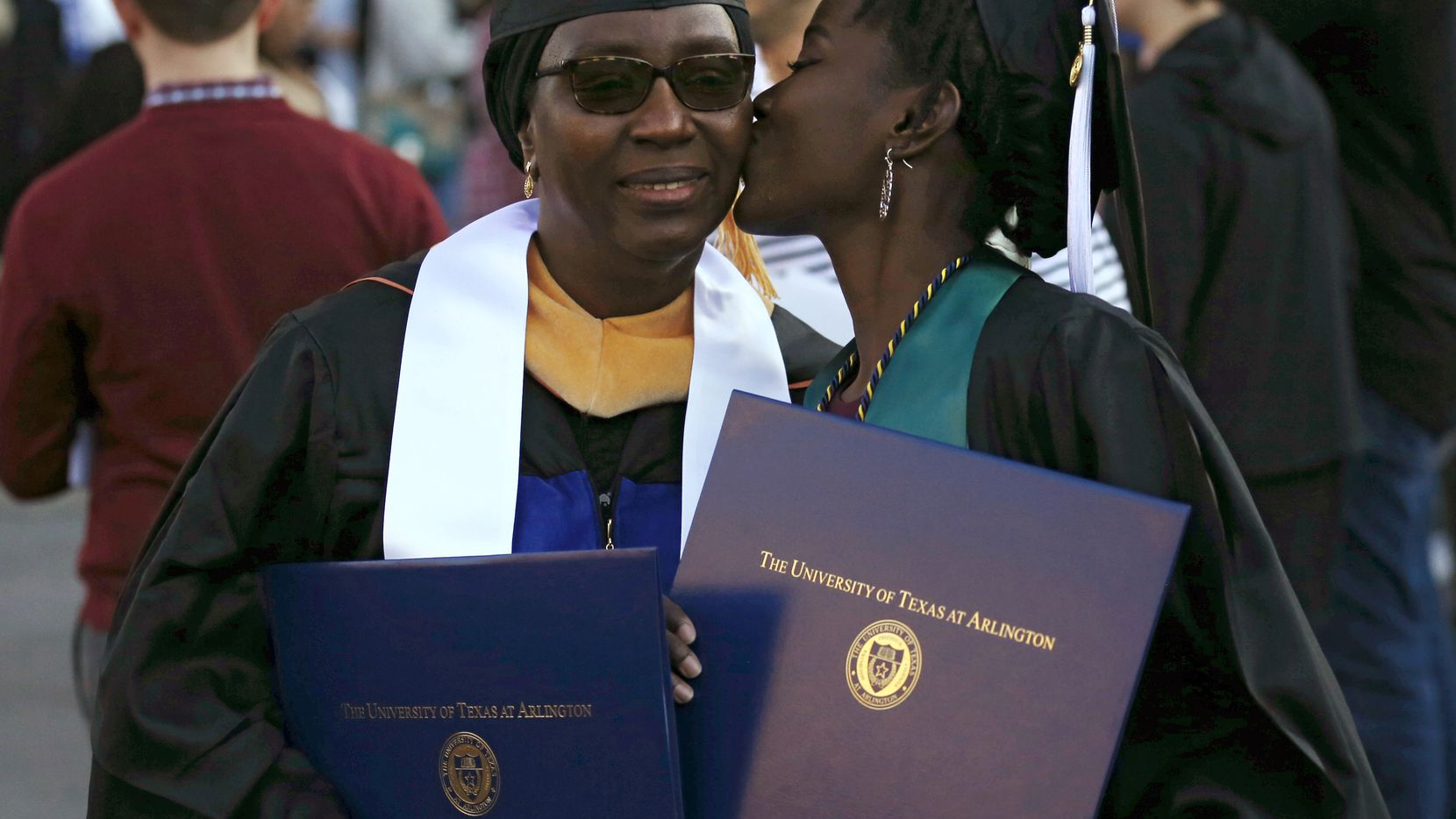 Ndeye Ndaw gets a kiss from her daughter Awa Sy as they take photos together after graduation ceremonies at the University of Texas at Arlington. Ndaw earned a master's degree and her daughter earned her bachelor's degree on the same day from UTA.