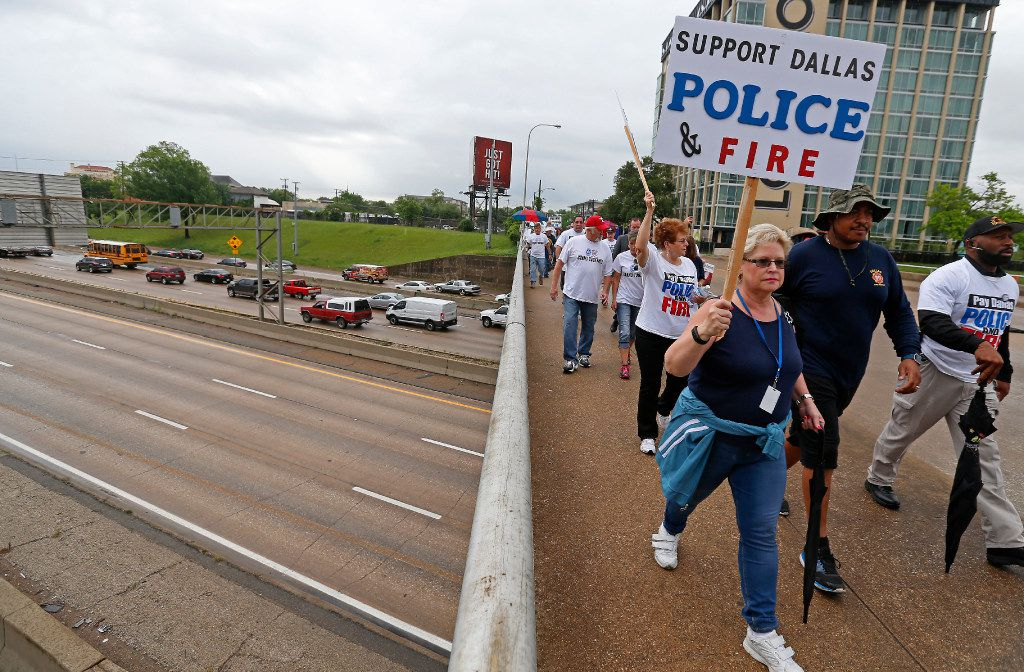 Dallas police and fire retirees march on Akard Street to City Hall in Dallas on April 26, 2017. They held a rally against Mayor Mike Rawlings' letter, which asked taxpayers to support in making changes to a proposed Dallas Police and Fire pension bailout, at the City Hall after the march.