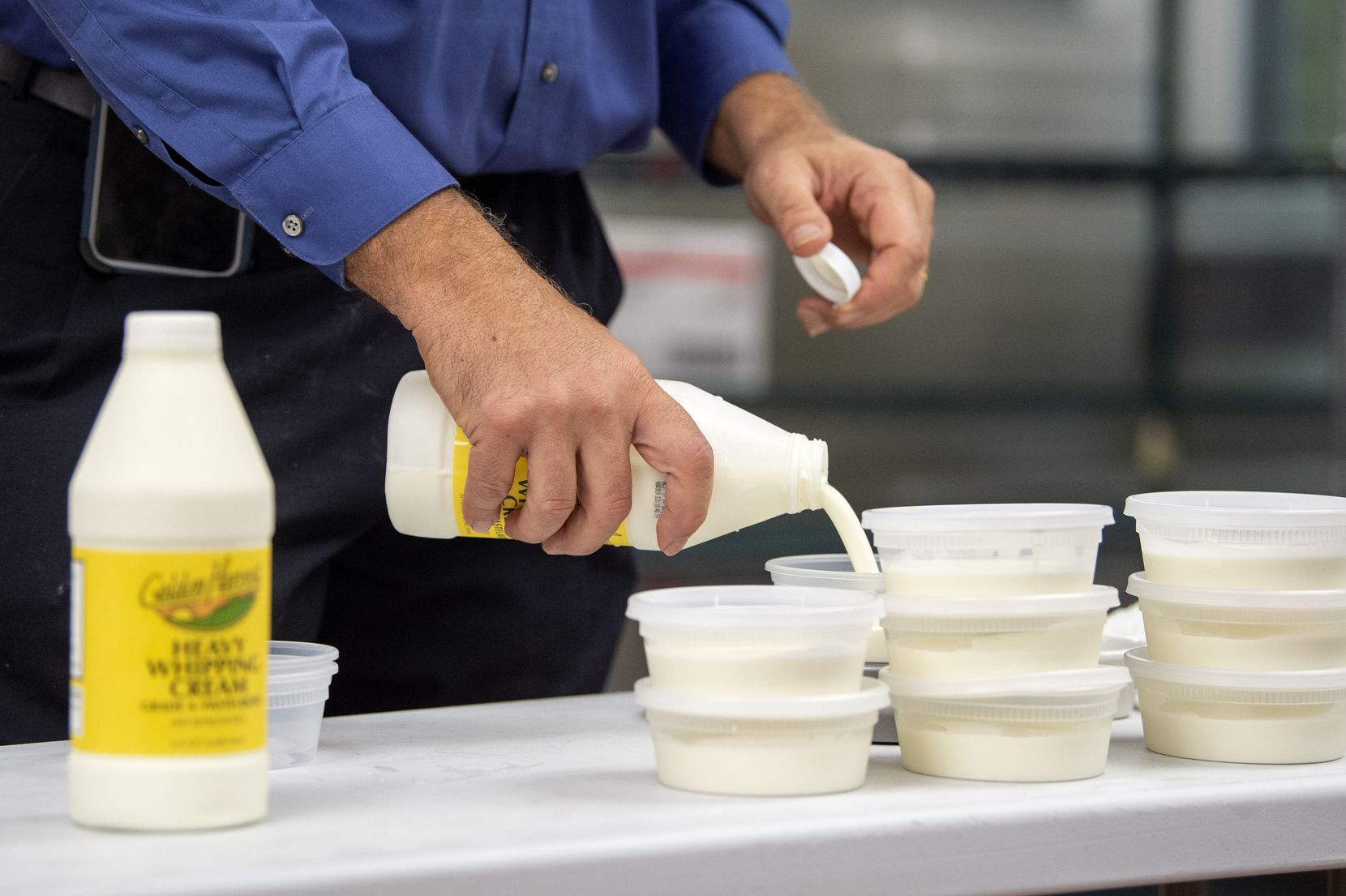 Garry Abbs, an instructional specialist of hospitality management at the Dallas College Culinary, Pastry and Hospitality Center, measures out whipping cream to be included in boxes of ingredients.