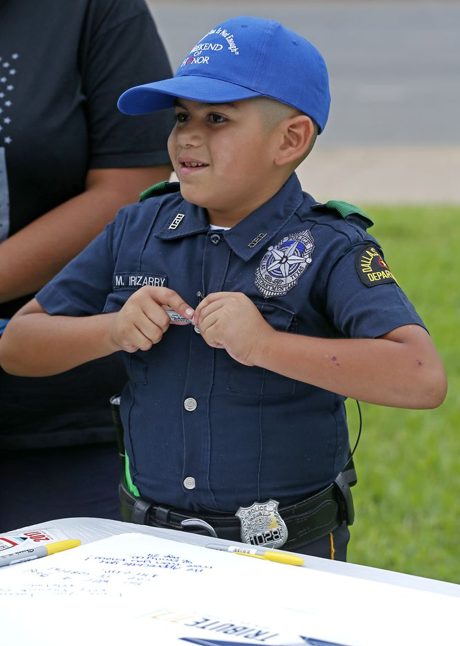 Melquiades Irizarry, 7, dressed as a Dallas Police officer, leaves a message during the Tribute 7/7 event.