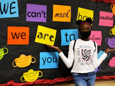 New East Middle School sixth grade student Terrani Edwards poses in front of signage campus staff put in place to welcome her and other students to campus.
