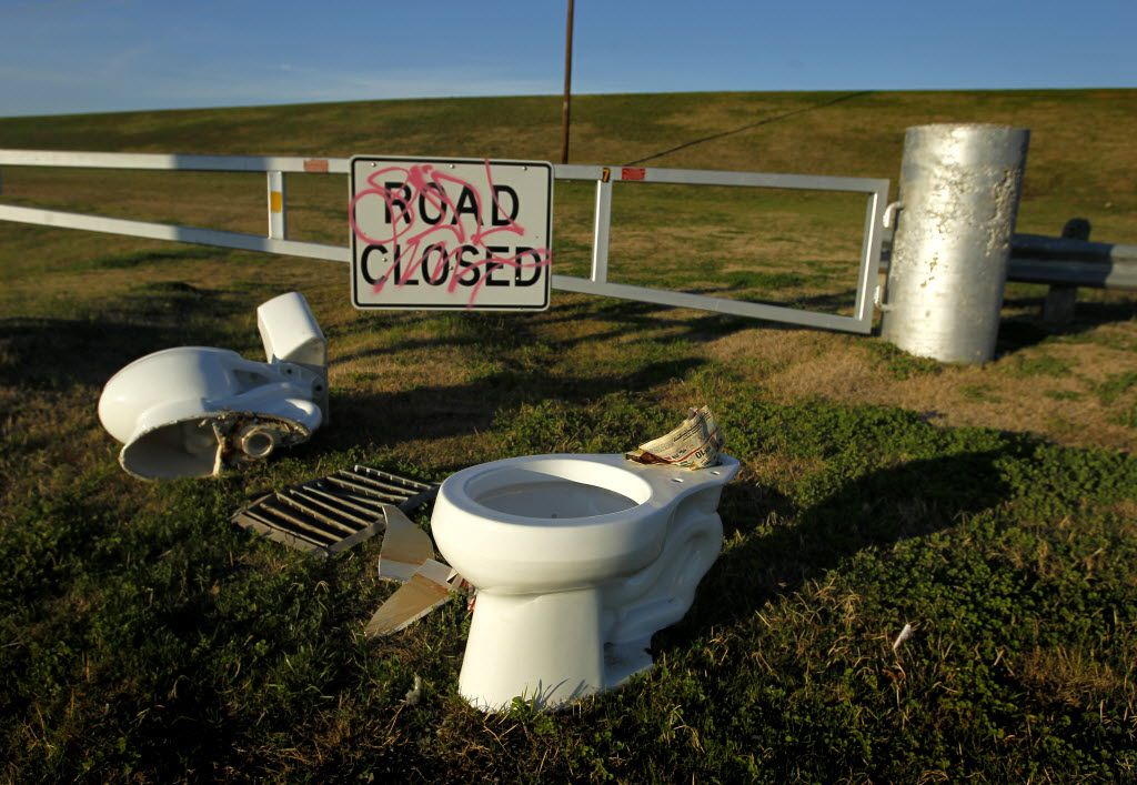 A pair of abandoned toilets lie next to a levee gate the West Levee of the Trinity River on Friday, December 16, 2011 just North and West of downtown Dallas, Texas off Canada Drive. (Brad Loper/The Dallas Morning News)