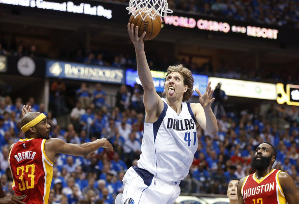 Dallas Mavericks forward Dirk Nowitzki (41) shoots  a layup in between Houston Rockets guard Corey Brewer (33) and Houston Rockets guard James Harden (13) during the first half of game 4 of the first round of the NBA playoffs at American Airlines Center in Dallas on Sunday, April 26, 2015. (Vernon Bryant/The Dallas Morning News)
