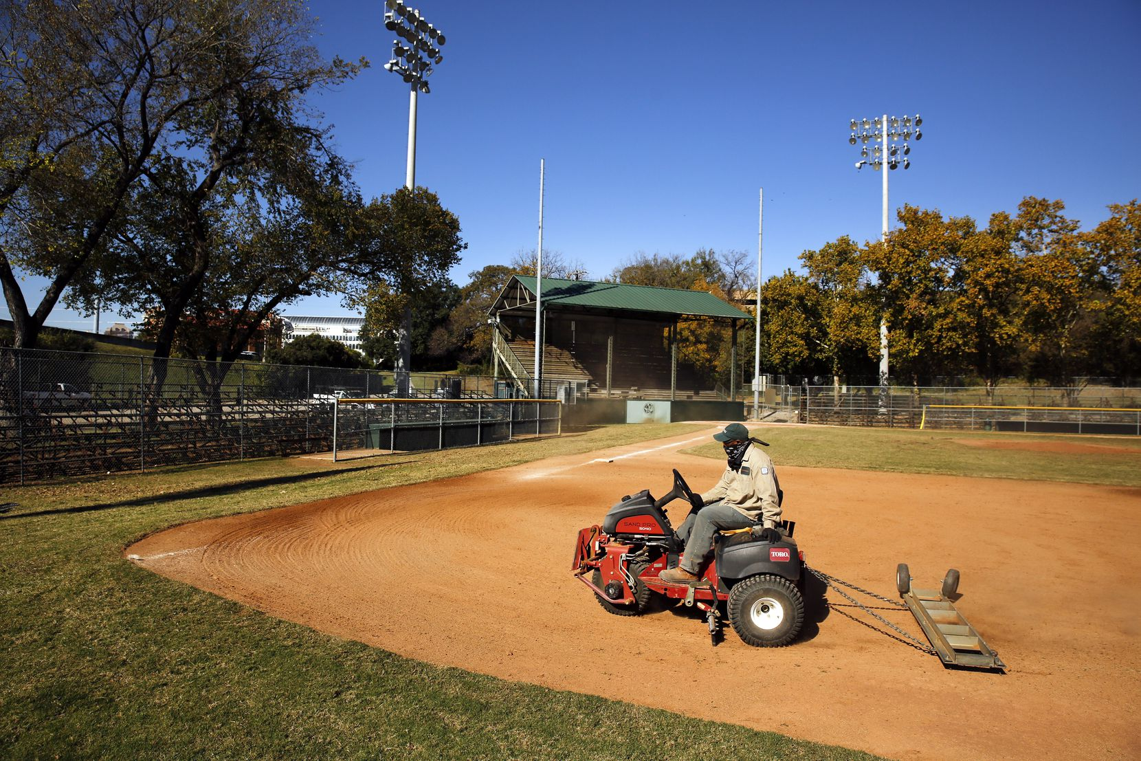 Lawrence Willie of the Dallas Park and Recreation Department rakes the Reverchon ballpark infield. Beginning in 2018, the facility was deemed sufficiently hazardous that North Dallas High School could no longer allow its Bulldogs baseball team to play there, but some community games continue at the park.