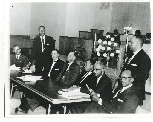 A panel discussion at New Hope Baptist Church in the 1960s brought together white and black leaders. Louis A. Bedford is standing at rear.