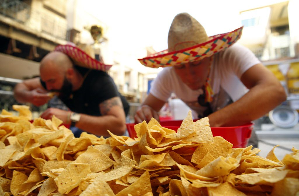 Mounds of chips are stacked on the table as competitors devour pounds of queso during an eating competition. In celebration of Cinco De Mayo, Mattito's Tex-Mex restaurant in Uptown area of Dallas held a quest eating competition, Thursday, May 5, 2016.  (Tom Fox/The Dallas Morning News)