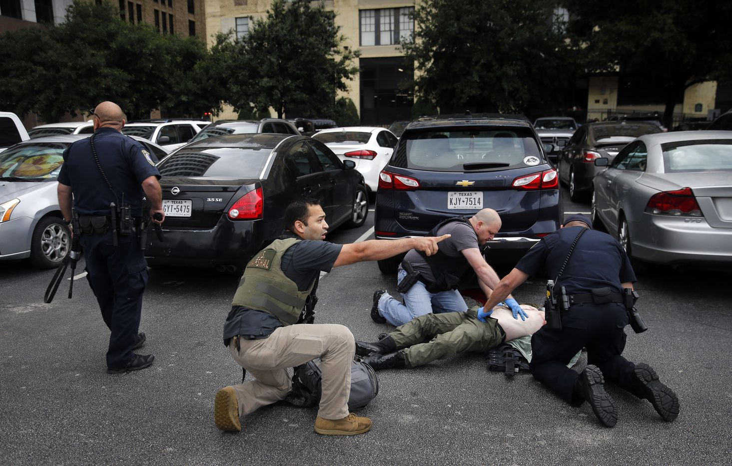 Law enforcement officers provide medical attention to shooter Brian Isaack Clyde after he col­lapsed in a downtown Dallas parking lot.
