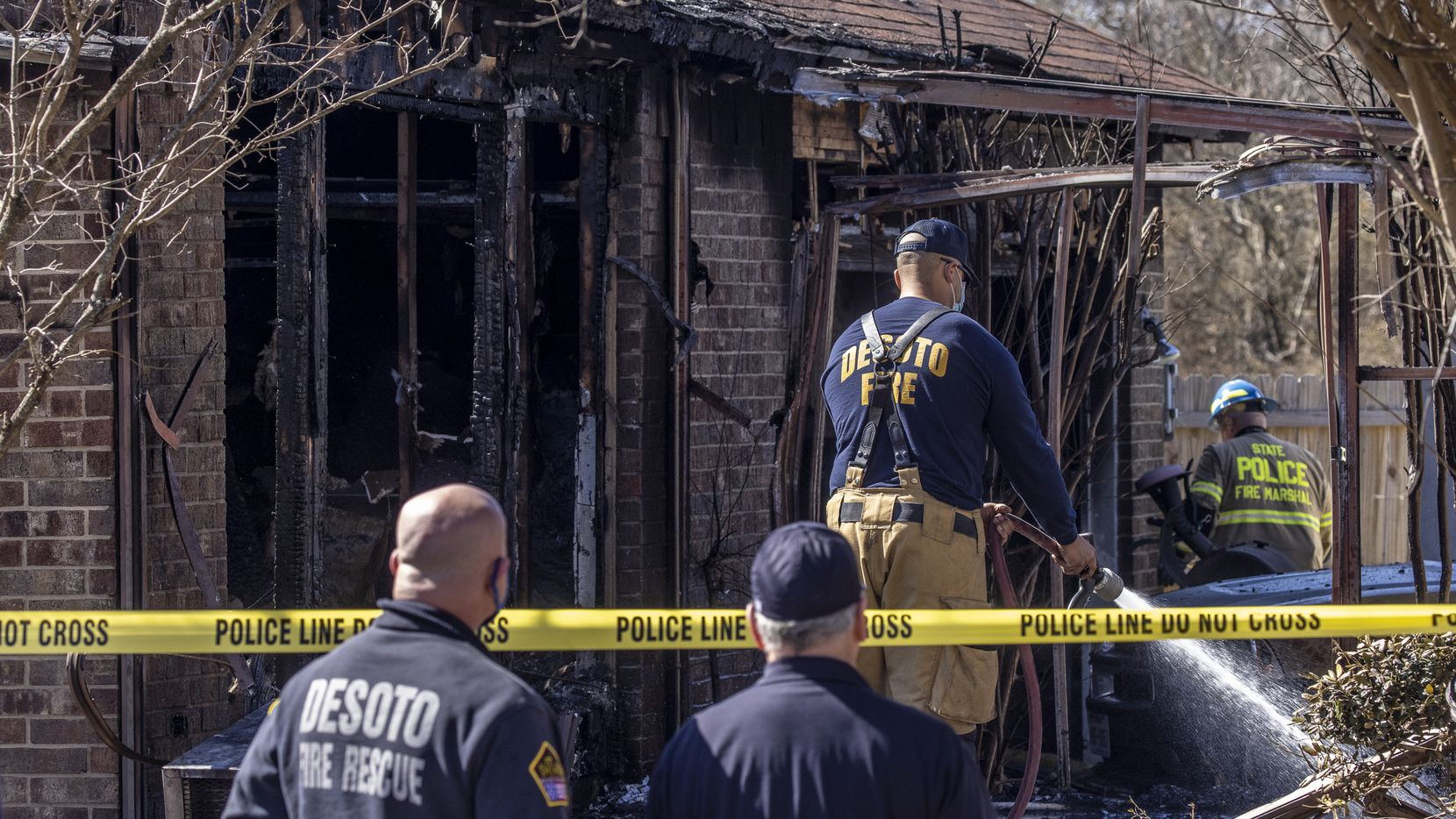 Personnel from the DeSoto Fire Department and the Texas State Fire Marshal investigate the aftermath of a house fire on the 100 block of Wildwood Court that claimed the lives of two small children, ages 1 and 2, on Tuesday morning, Feb. 23, 2021. (Lynda M. González/The Dallas Morning News)