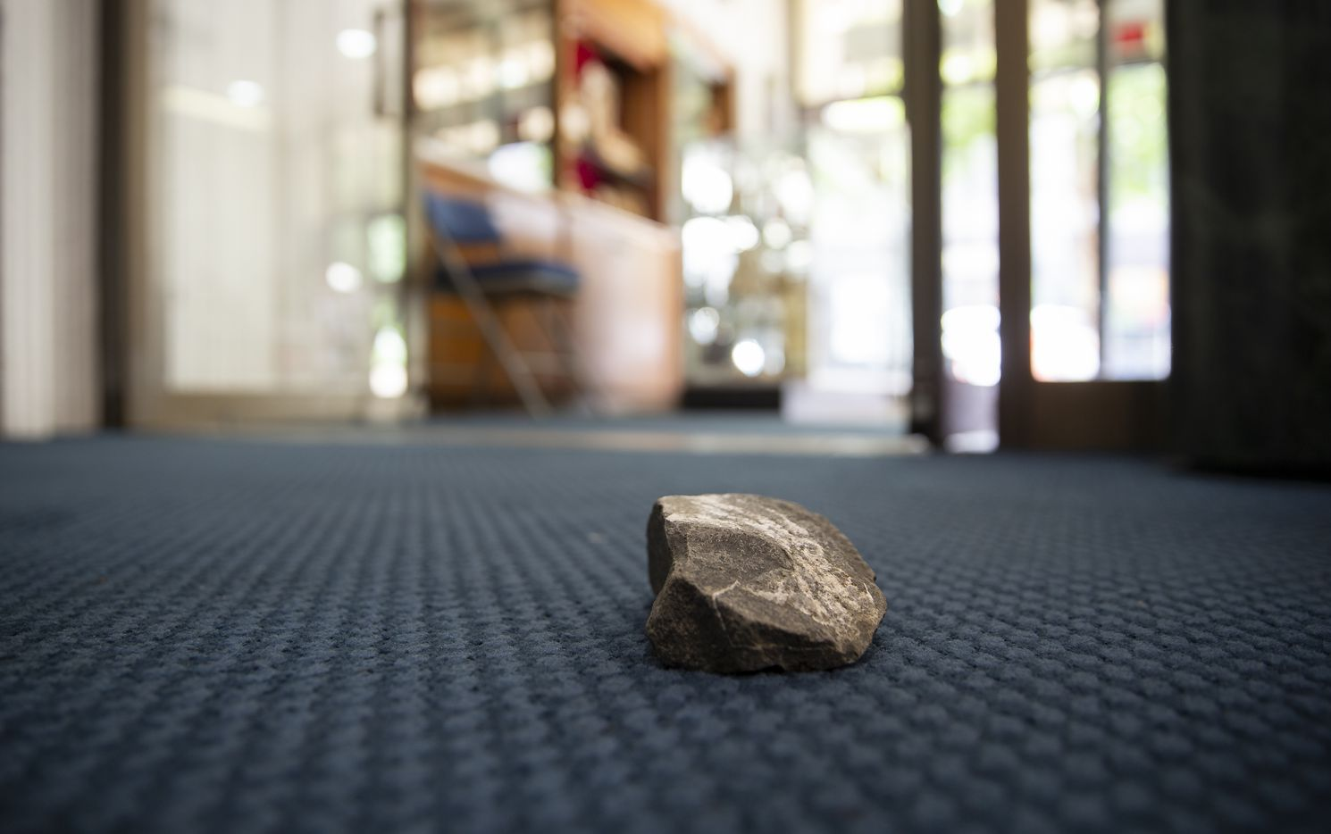 A rock that was thrown through a window at St. Jude Chapel remains Saturday morning, May 30, 2020, in Downtown Dallas. The chapel on Main St. was hit during last night's protest.