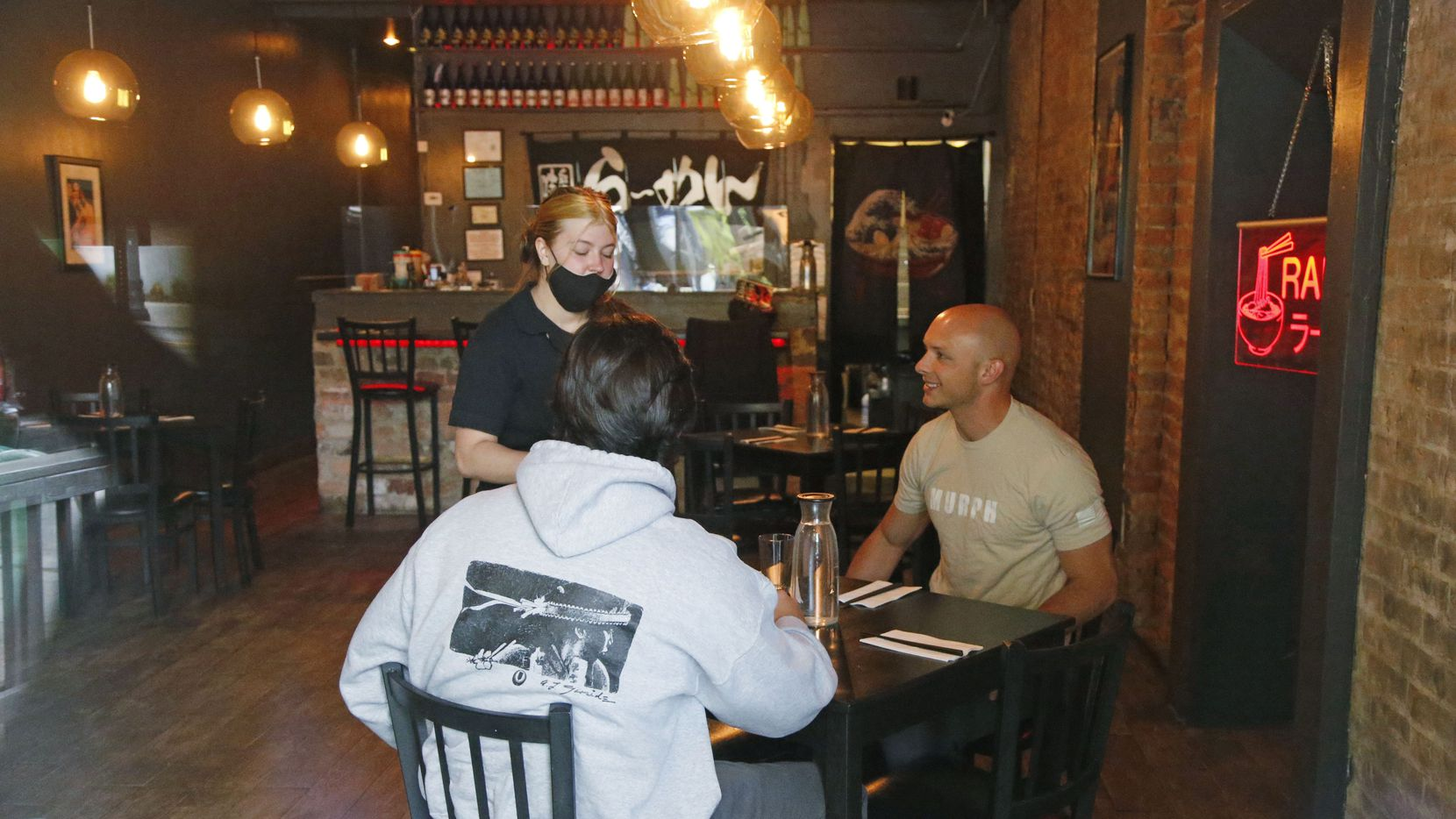 A server took an order at the Ramen Bar on May 1 in Salt Lake City. Shani and Serge Oveson were excited to reopen dine-in seating at their small downtown Salt Lake City restaurant that had seen an 85% drop in sales since mid-March after eateries across Utah were limited to offering takeout orders to prevent the spread of the coronavirus.