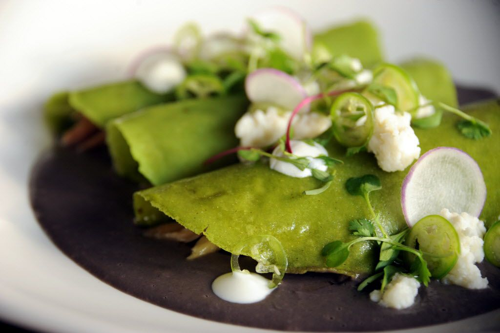 Madrina's enfrijolada is made with confit, cilantro tortilla, serrano chile, black bean puree, and ricotta cheese.