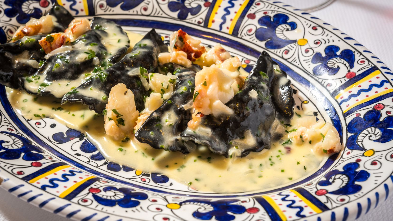 When New York style Italian restaurant Carbone opens in Dallas, it'll serve pasta, salad and more in a glamorous dining room. The mezzaluna is lobster and shrimp ravioli made with a squid ink dough and served in tarragon cream sauce.