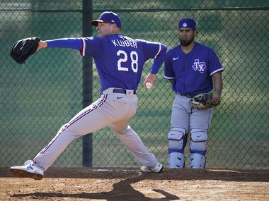 Texas Rangers pitcher Corey Kluber throws in the bullpen as catcher Robinson Chirinos looks on during the first spring training workout for pitchers and catchers at the team's training facility on Wednesday, Feb. 12, 2020, in Surprise, Ariz.