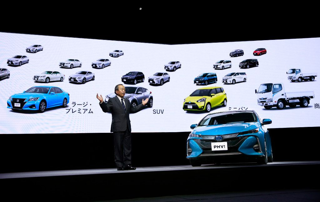 Toyota Motor Corporation's Chairman of the Board of Directors Takeshi Uchiyamada speaks with a Toyota new Prius PHV plug-in hybrid during a press conference rolling out the new Prius PHV in Tokyo, Wednesday, Feb. 15, 2017. Toyota has revamped its plug-in hybrid with a longer cruise range and quicker charging, including from a regular home plug, hoping it will sell better than the first model from five years ago that officials acknowledged had flopped. (AP Photo/Shizuo Kambayashi)