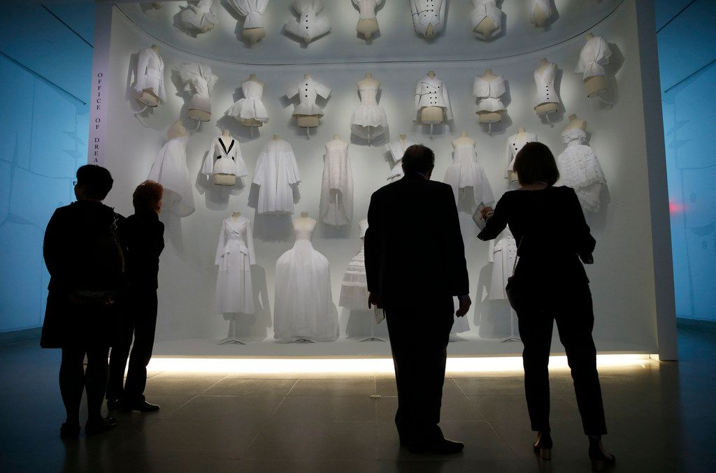 """Visitors look at some of the Dior pieces in the """"Office of Dreams"""" area of the fashion exhibition """"Dior: From Paris to the World"""" at the Dallas Museum of Art."""