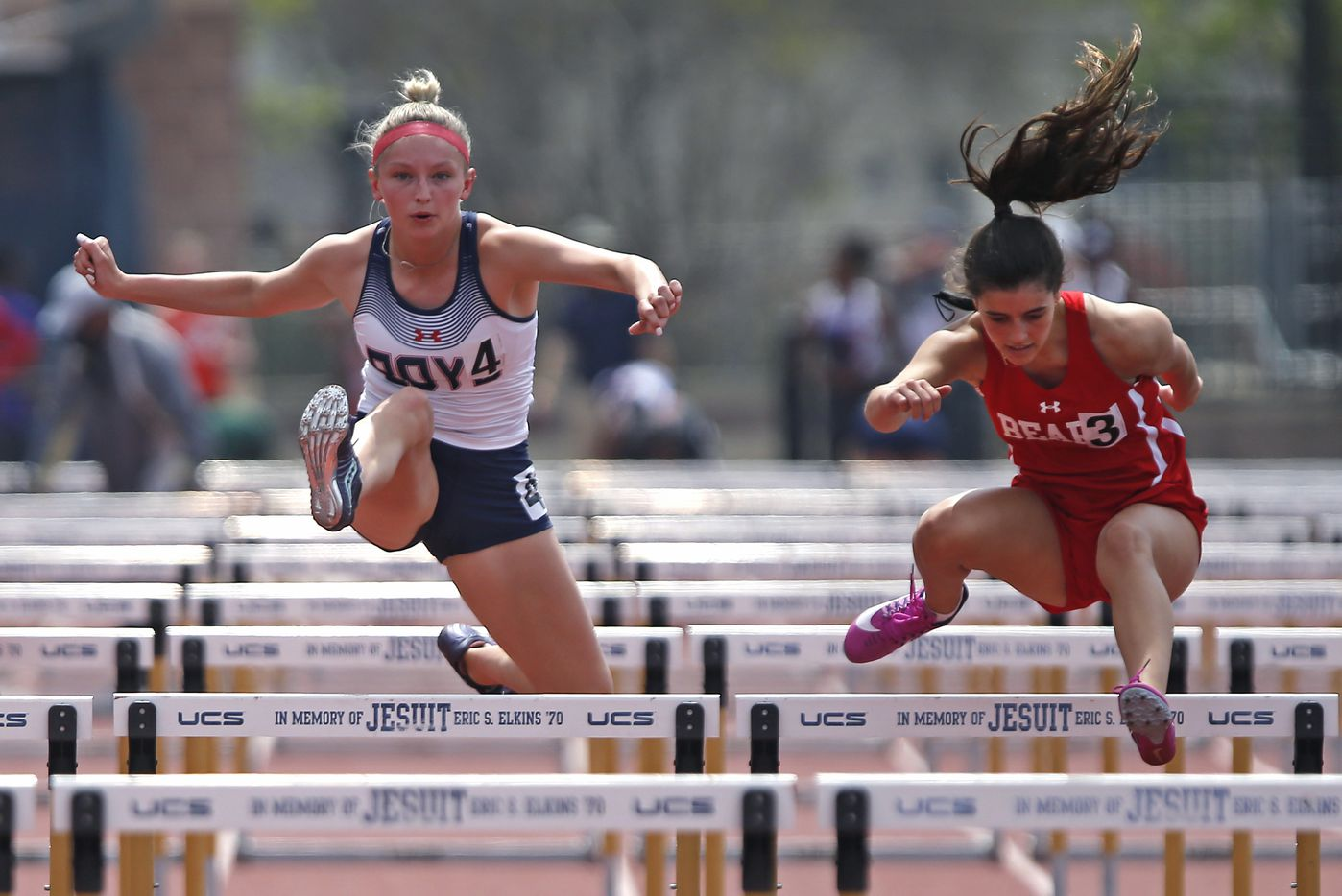 McKinney Boyd High School's Delaney Goheen (left), 17, competes with Emi Diaz, 14, of Ursuline Academy in the 100 hurdels during the Jesuit-Sheaner Relays held at Jesuit College Preparatory School in Dallas on Saturday, March 27, 2021.  (Stewart F. House/Special Contributor)