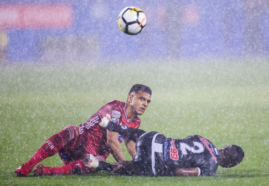 FC Dallas forward Cristian Colman (9) and Tauro F.C.'s Rigoberto Nino (2) watch the ball fly away after they slip in the rain during the second half of a CCL Leg 2 game between FC Dallas and Tauro FC on Wednesday, February 28, 2018 at Toyota Stadium in Frisco, Texas. (Ashley Landis/The Dallas Morning News)