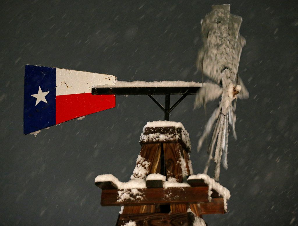 A windmill with snow Thursday Dec. 7, 2017 in Leon Springs, Texas.