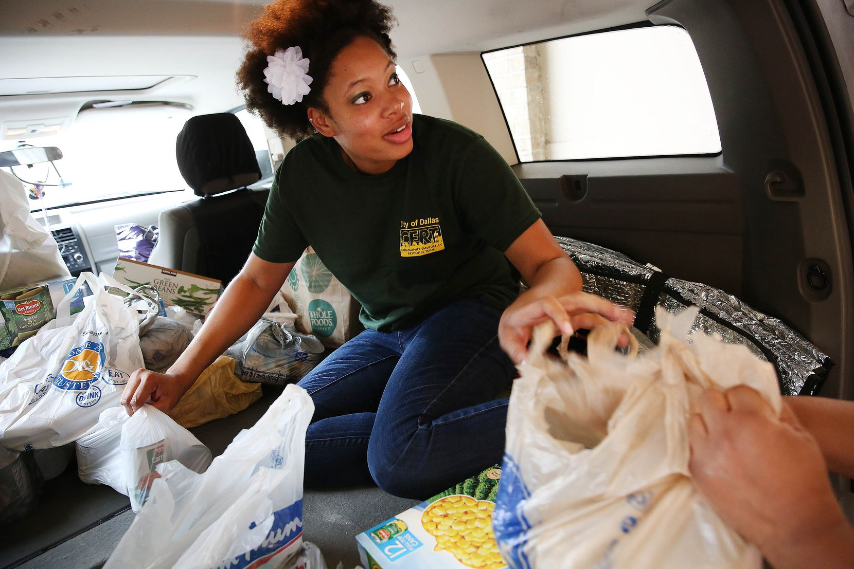 Alyce Mark, of Christian Chapel Temple of Faith, helps to unload donations at a drop off location of Trusted World donations for Hurricane Harvey relief in Dallas on Sunday.