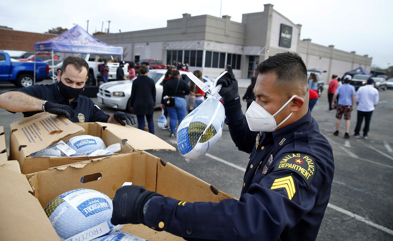Dallas Police Department Unidos outreach team members Sgt. Eddie Reyes (right) and Lt. Stephen Williams unload frozen turkeys for volunteers from First United Bank, Hunger Busters and Canales Furniture during a Thanksgiving turkey handout in Pleasant Grove on Nov. 21. In the last year, the Unidos team has grown to have Spanish-speaking officers at every patrol division. The group has been working to build trust between the Latino community and police for the past five years.