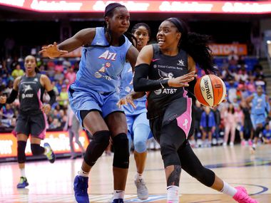 Dallas Wings guard Arike Ogunbowale (24) is covered by Atlanta Dream center Elizabeth Williams (1) as she drives for a lay up during the fourth quarter at College Park Center in Arlington, Texas, Sunday, August 25, 2019. Despite their comeback in the fourth quarter, the Wings fell to the Dream, 77-73.