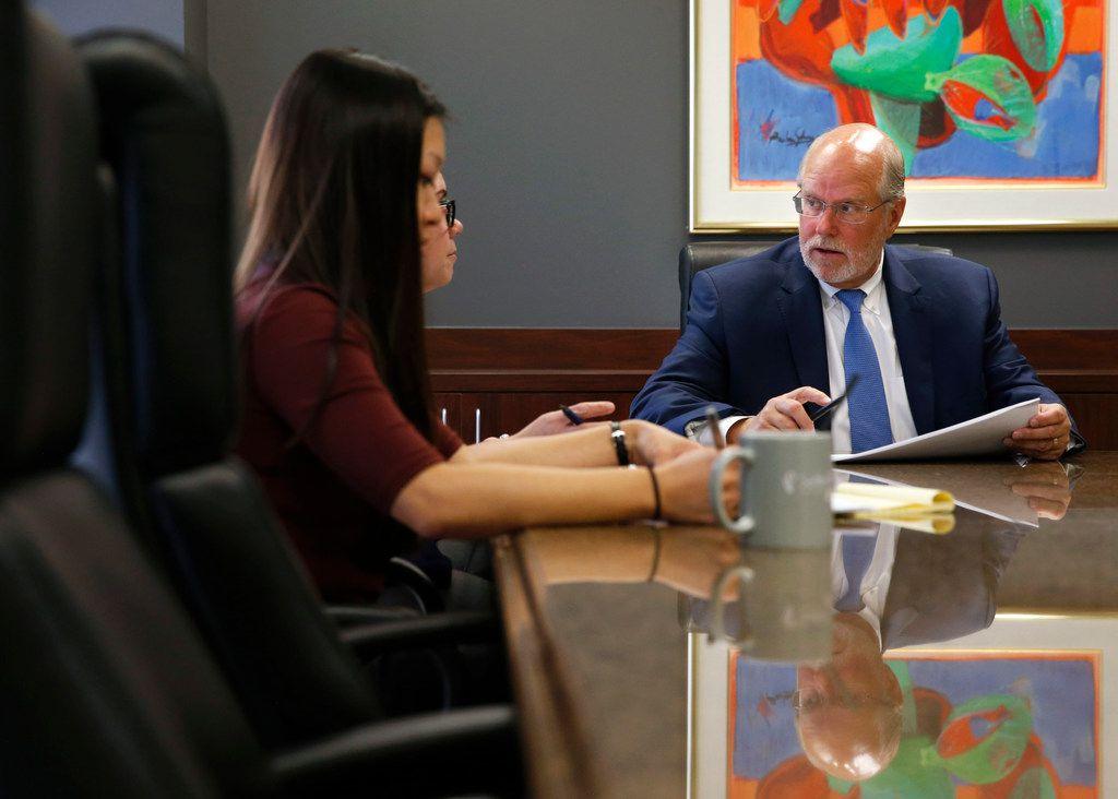 "SettlePou cofounder John D. ""Jay"" Settle talks with Rebekah Wilson, a legal secretary, as associate attorny Jillian Loh (left front) listens during a meeting at SettlePou in Dallas."