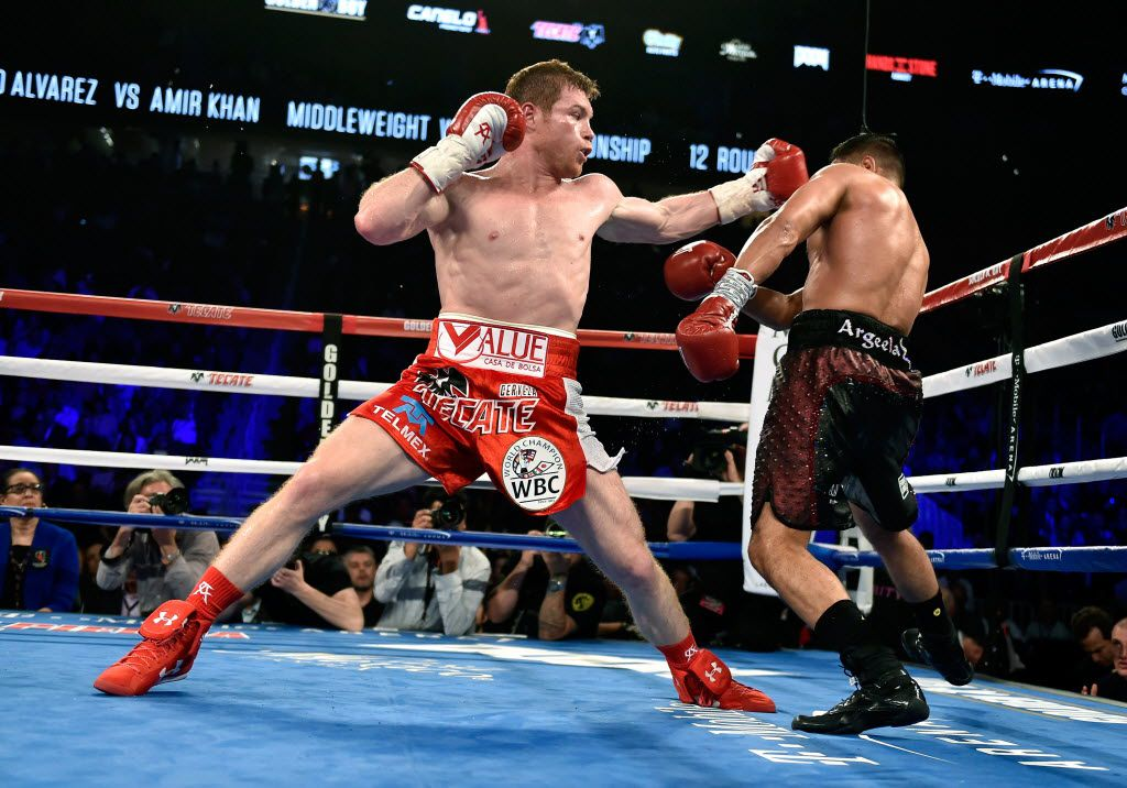 LAS VEGAS, NEVADA - MAY 07:  Canelo Alvarez (L) battles with Amir Khan during a WBC middleweight title fight at T-Mobile Arena on May 7, 2016 in Las Vegas, Nevada. Alvarez won by a sixth round knockout.