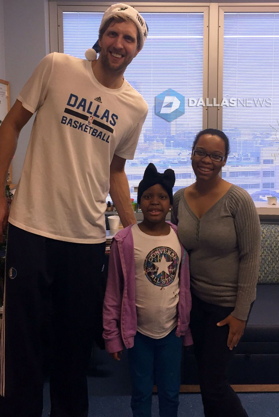 Dirk Nowitzki poses with patient Legecy Allen, 7, and her mother, Roseland Allen, at Children's Medical Center. Legecy, who marveled at Dirk's height when he visited her, has been hospitalized since Sept. 7.