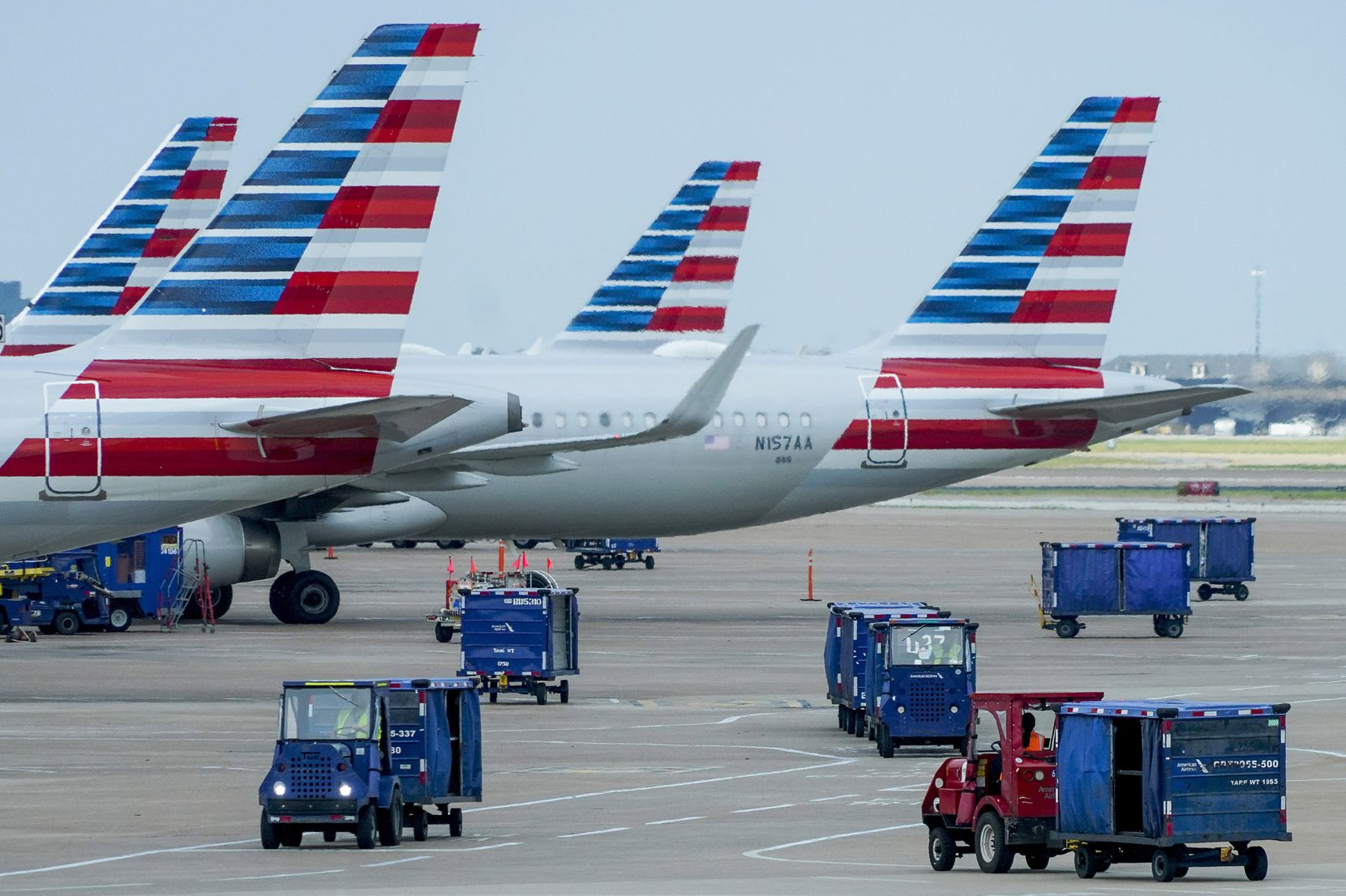 Baggage carts drive on the tarmac near American Airlines planes at the gates of Terminal C at DFW International Airport.