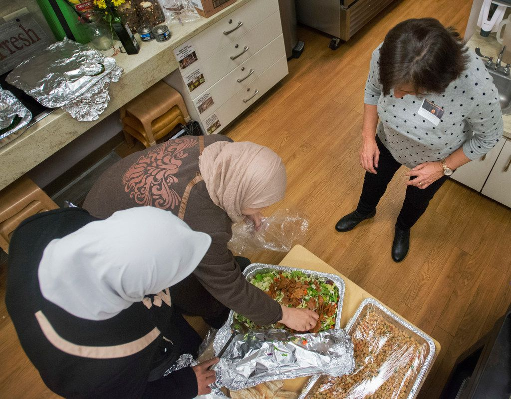 Syrian refugees Maryam Alhow, left, and Mariam Alshiblaq, center, aided by friend and interpreter Rania Stanbouly, prepare a salad at the Leah's Kitchen annual Thanksgiving Community Meal at Temple Emanu-El in Dallas on Nov. 16.