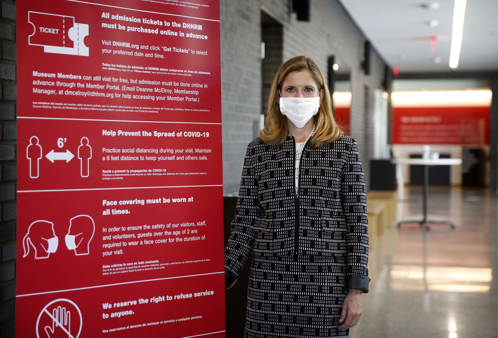 Mary Pat Higgins, president and CEO of the Dallas Holocaust and Human Rights Museum in Dallas, poses next to a COVID precautions sign, Friday, Aug. 7, 2020.