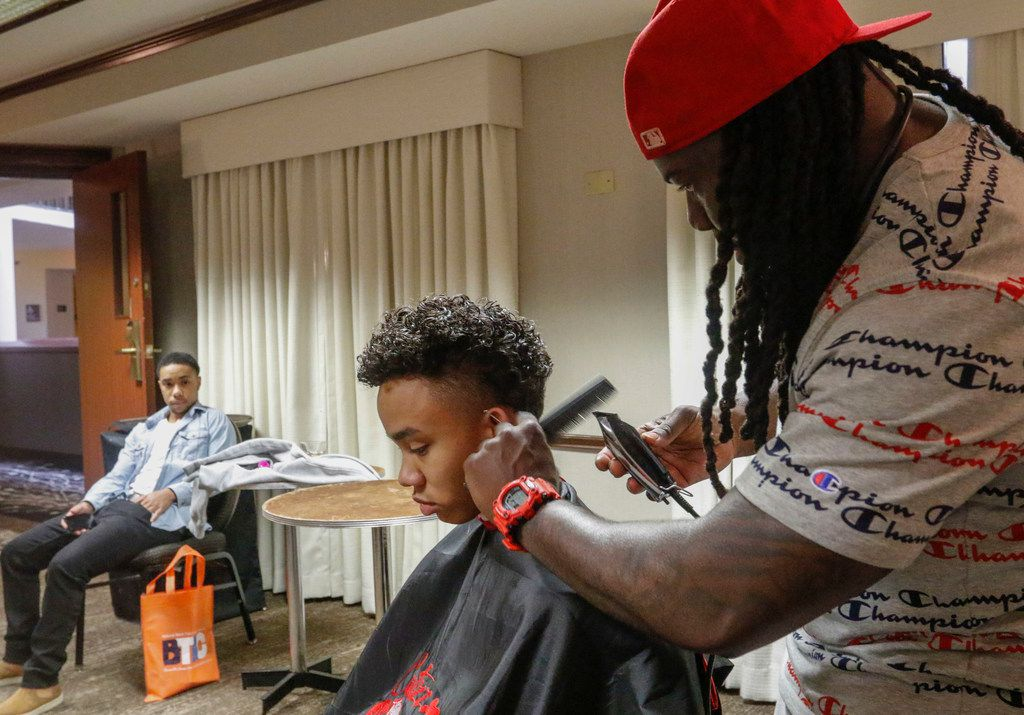 Daevion Jordan watches Tai Jordan have his hair cut at the Black Trans Advocacy Conference.
