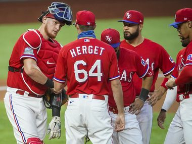 FILE - Rangers reliever Jimmy Herget gets a visit from catcher Sam Huff, second baseman Rougned Odor, third baseman Isiah Kiner-Falefa and first baseman Ronald Guzman as he enters the game in the first inning against the A's at Globe Life Field on Friday, Sept. 11, 2020.