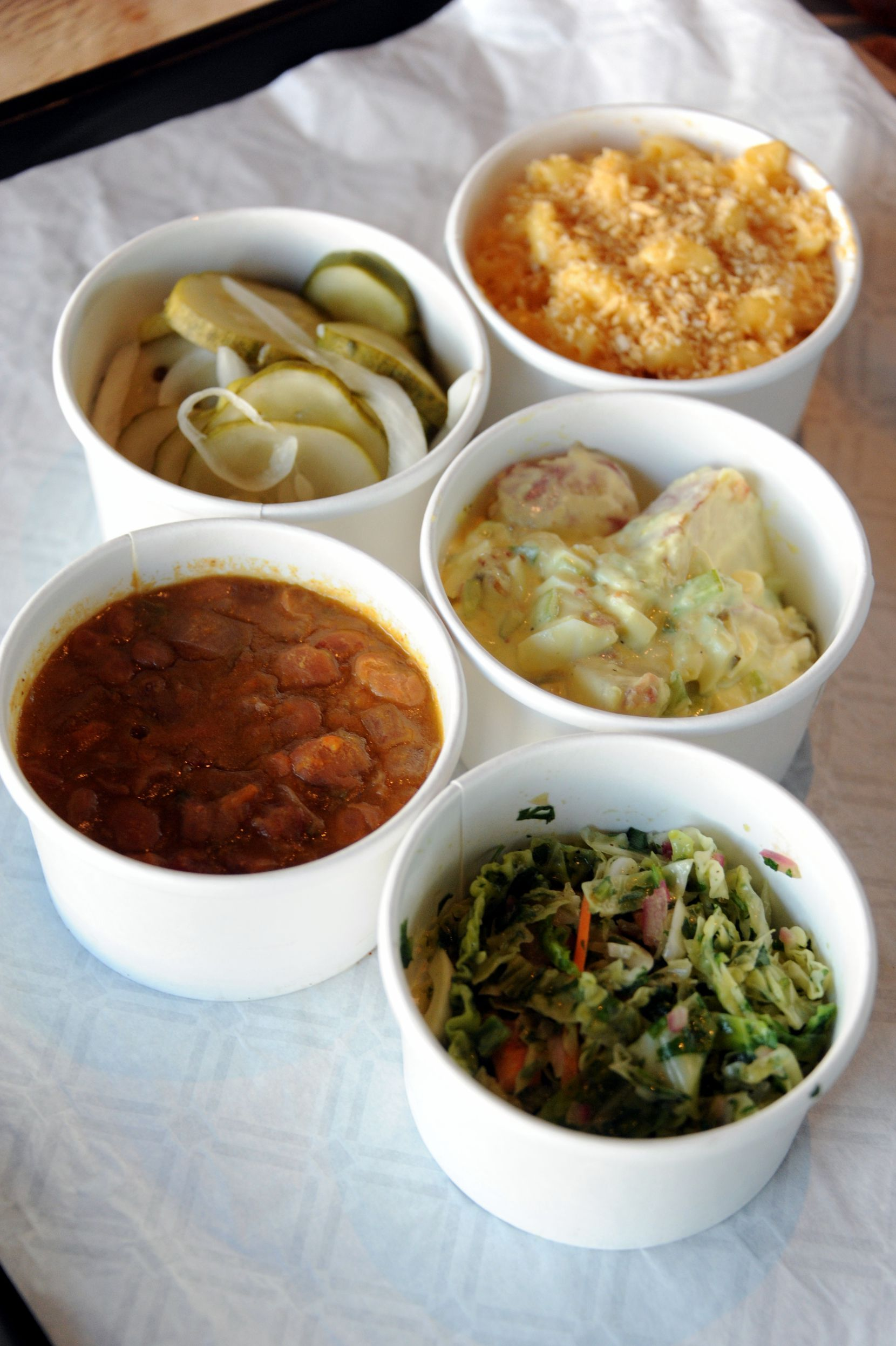 Guests can choose sides such as coleslaw, beans, potato salad, mac n' cheese and house-made pickles at Ten 50 BBQ in Richardson.