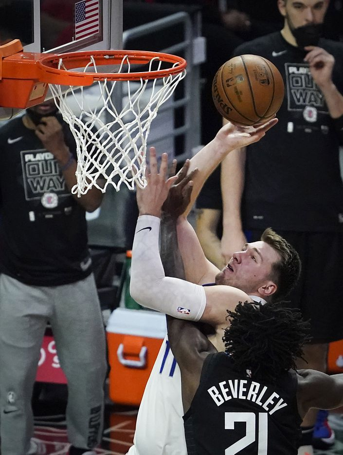 Dallas Mavericks guard Luka Doncic (77) scores past LA Clippers guard Patrick Beverley (21) during the second half of an NBA playoff basketball game at Staples Center on Tuesday, May 25, 2021, in Los Angeles. The Mavericks won the game 127-121.