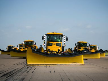 Snow plows make their down a runway during a training on how to quickly and efficiently clear runways at DFW International Airport.