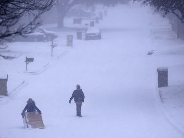 Kids improvised by sledding on large pieces of cardboard down a steep, snow-covered street this week.