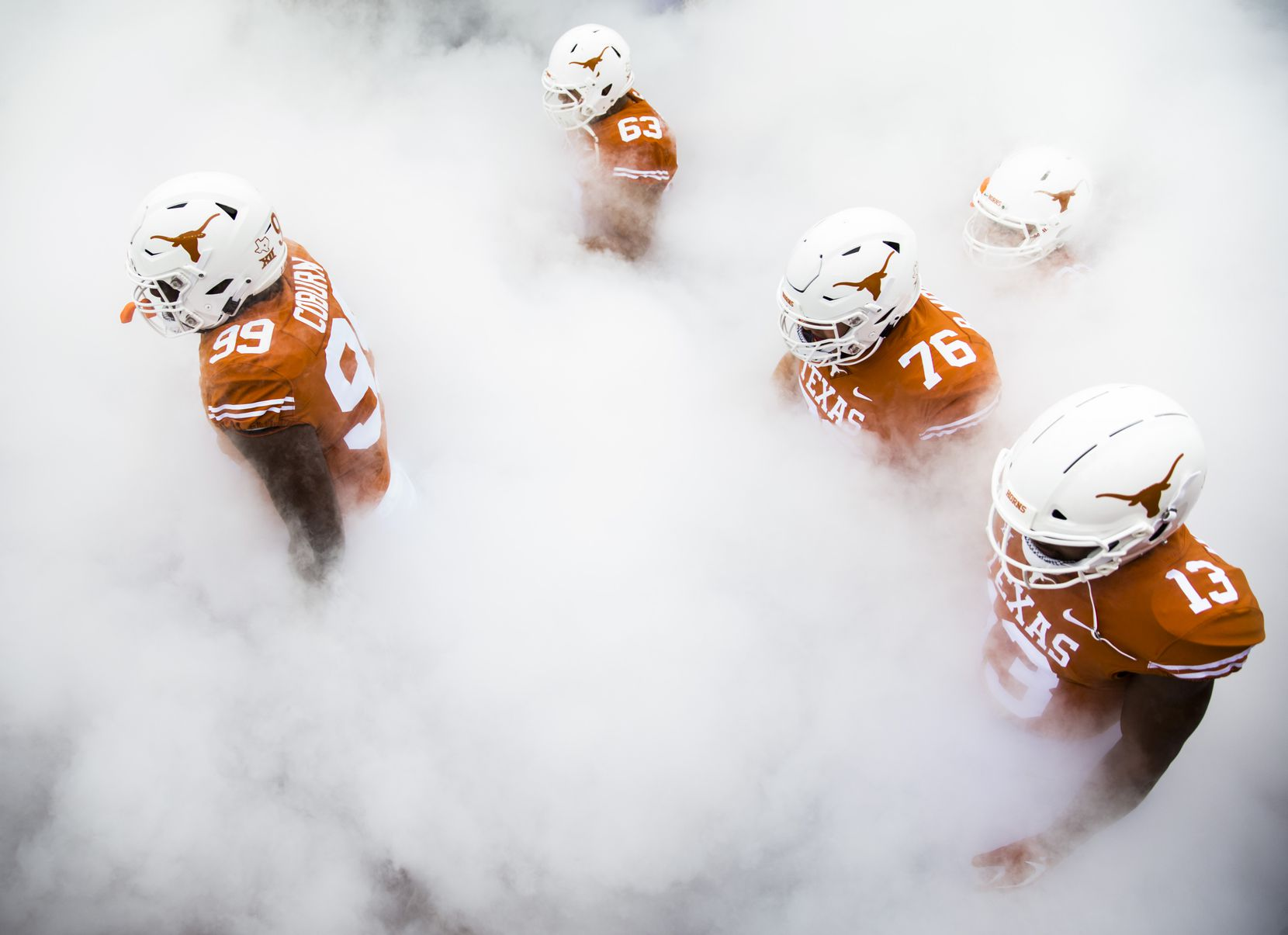 Members of the Texas Longhorns football team walk through smoke to enter the stadium before a game between TCU and the University of Texas on September 22, 2018 at Darrell K Royal - Texas Memorial Stadium in Austin.