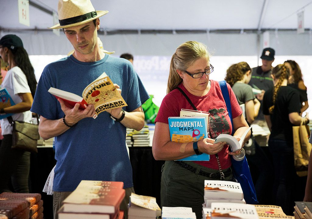 Ryland Trahan and Melissa McFarlin examine books inside a sales tent during the Texas Book Festival in Austin  on Saturday, Nov. 4, 2017.