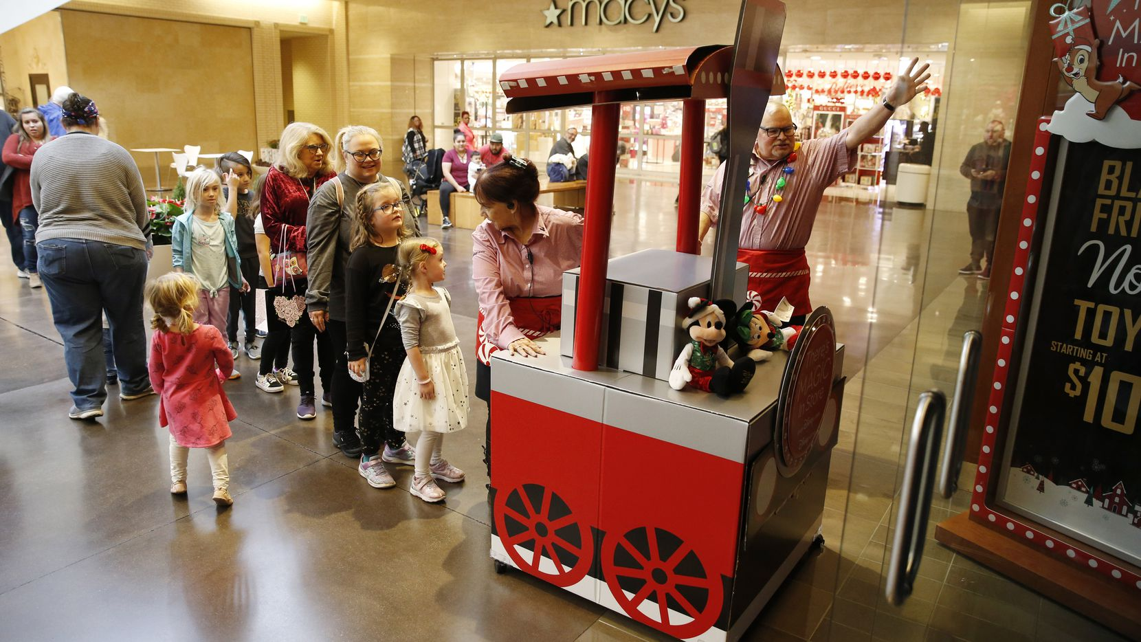 Disney Store employee Gary Prophet holds the door as Sandra Biggs leads the parade into the store signifying the opening of the store at NorthPark Center in Dallas on Wednesday, November 27, 2019.