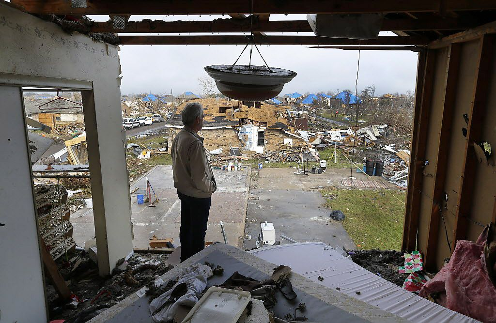 From the second floor of a neighbor's damaged home, Gary Hale looks out at the lot where his home stood before a tornado swept through his Rowlett neighborhood on Dec. 26, 2015. Mental health experts warn that tornado victims are at risk for post-traumatic stress disorder.